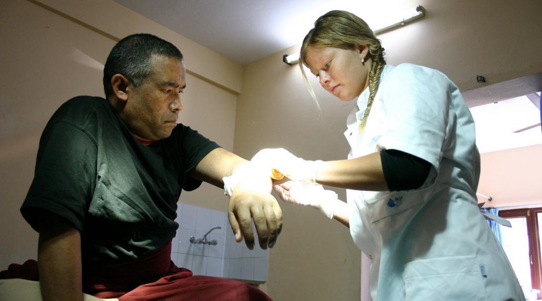 Una interna de Medicina limpiando heridas de un paciente local durante sus prácticas médicas en Nepal.